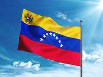 Venezuela-Flagge mit Wappen wellenartig bewegend in den blauen Himmel Stockfotos