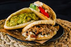 Venezuelan arepas on a black background, made with maize and filled with avocado, tomato, meat, cheese and black beans
