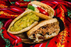 Venezuelan arepas on a colorful background, made with maize and filled with avocado, tomato, meat, cheese and black beans