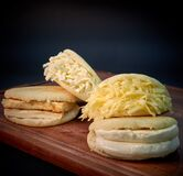 Venezuelan arepas filled with different types of cheese with wooden board