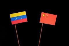 Venezuelan flag with Chinese flag on black stock photos