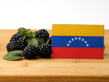Venezuelan flag on a wooden panel with blackberries isolated on stock images