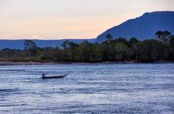 Venezuelansk indier i kanoten som paddlar i floden arkivfoton