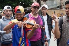 Venezuelansk violinist Wuilly Arteaga som spelar hans fiol under protest i Caracas Royaltyfri Foto