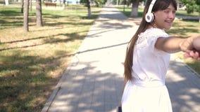 venga despu?s de m? La muchacha en auriculares sonr?e y lleva al hombre querido por la mano en el parque un d?a de primavera trab almacen de metraje de vídeo