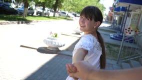 venha ap?s mim Curso da menina e do noivo guardando as m?os Movimento lento a menina bonita conduz seu homem amado pela mão video estoque