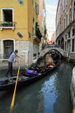 Venice. Gondolier in a gondola floating narrow channel Stock Image