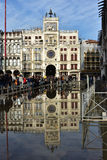 Venice Acqua Alta. High tide flooding Saint Mark Square in Venice and tourists walking on footbridge before the famous Clock Tower Stock Photo