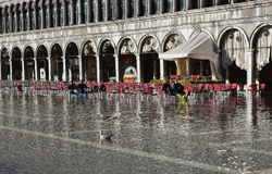 Venice Acqua Alta. High tide flooding Saint Mark Square in Venice, turists relaxing on chairs in the water Stock Photo