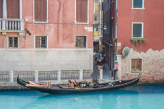 Venice as it is - city on water, Gondola parked in canal and gondolier in traditional shirt and painted face waiting for Stock Photo