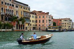 VENICE - AUGUST 25. two men on a motor boat floating on the Gran Stock Image