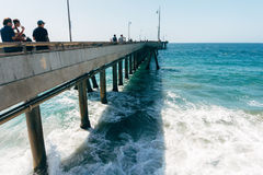 Venice beach pier and the people walking on it in California USA. Ocean foam and waves. Surfers in ocean Stock Photo
