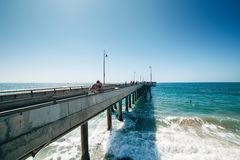 Venice beach pier and the people walking on it in California USA. Ocean foam and waves. Surfers in ocean Royalty Free Stock Photo