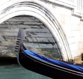 Venice, bow of gondola under the bridge in the waterway Stock Image