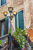 Venice building facade with flowers and lamps Stock Photos