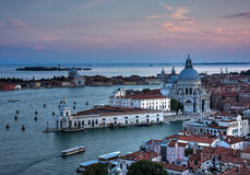 Venice buildings and canal in the sunset. Lagoon in the distance, and transportation boats in the canal Royalty Free Stock Photos