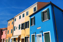 Venice, Burano island canal, small colored houses and the boats Stock Photos