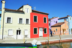 Venice Burano with its typical colorful houses, boat and tourists, in sunny afternoon, Venice, Italy Stock Image