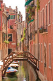 Venice canal. A view of a Venice canal with boats and wooden bridge Royalty Free Stock Photography