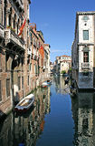Venice Canal. Scenic view of old buildings reflecting on canal with boats moored by waterfront homes, Venice, Veneto, Italy Stock Photography