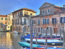 Venice canal with beautifully colored houses. A typical canal in Venice with beautifully colored houses. Every owner has it's own boat which is his primary means Stock Photos