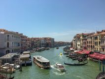 Venice canal with boats and gondoliers royalty free stock images