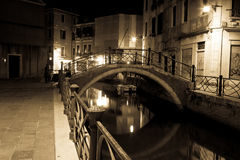 Venice canal late at night with street light illuminating bridge Royalty Free Stock Image