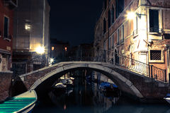 Venice canal late at night with street light illuminating bridge Stock Images
