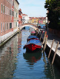 Venice canal with red boat and bridge Royalty Free Stock Photography