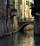 Venice - Canal Series. A sunlit canal in Venice with a small bridge crossing Royalty Free Stock Photos