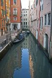 Venice canal with taxi riders stock photography