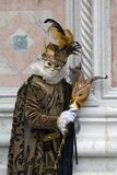 Venice mask dressed in a brown and gold costume at Venice Carnival in February, Venice Italy stock images
