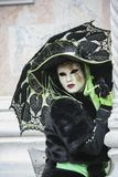 Venice Carnival character dressed in a colourful black and green and venetian mask Venice Italy royalty free stock photography