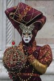 Venice Carnival character dressed in a colourful red and gold costume and Venice mask in February Venice Italy royalty free stock photos