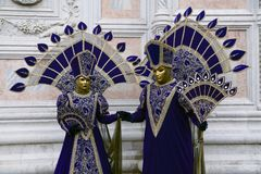 Venice Carnival costumes in purple and gold and Venice masks in February Venice Italy royalty free stock photography