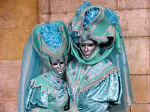 Venice Carnival: Couple in turquoise costumes. Carnival of Venice, Italy: Couple wearing beautiful masks and turquoise costumes in front of a marble wall Stock Photos