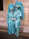 Venice Carnival: Couple in turquoise costumes. Carnival of Venice, Italy: Couple wearing beautiful masks and turquoise costumes in front of a marble wall Royalty Free Stock Photo