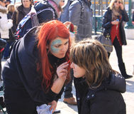 Venice Carnival, face painting. Editorial usefulness, a woman paints a tourist face outdoor at Venice carnival stock photo