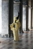 Venice Carnival Figure Venice Italy. Venice Carnival Character wearing a colorful vintage deco yellow and black carnival costume and mask with the pillars of Royalty Free Stock Image