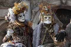 Venice Carnival Figures in a colorful gold and brown costumes and Venetian masks Venice Italy royalty free stock photo