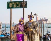 2017 Venice Carnival, Italy. Couple at lagoon with gondola sign Stock Photo
