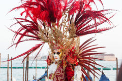 2017 Venice Carnival, Italy. Dramatic red feather mask and headd Royalty Free Stock Photo