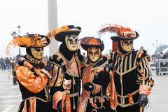 Venice Carnival, Italy. Four people in cat masks  in Piazza San Marco. 2017 Venice Carnival, Veneto, Italy. group of four people in orange and black cat costumes Stock Photo