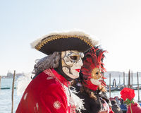 Venice Carnival, Italy. Man in tricorn hat and ornate mask at lagoon. 2017 Venice Carnival, Veneto, Italy. Man in classical tricorn hat and red jacket with Stock Photo