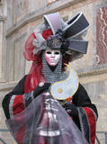 Venice Carnival: mask with armour. Carnival of Venice, Italy: Person wearing beautiful mask and costume in the colors dark red, silver, gray and black. Costume Stock Photo