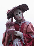Venice Carnival: mask and birdcage. Carnival of Venice, Italy: Woman wearing beautiful mask and costume in the colors red, pink and white. She's holding a Stock Photography