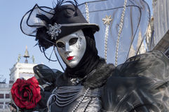 Venice Carnival Mask. A black dressed woman offering a red rose in San Marco square, Venice, Italy Royalty Free Stock Photo