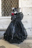 Venice Carnival Mask. Black lady with a red rose, posing at Venice Carnival, Italy royalty free stock images
