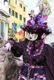 Venice Carnival Mask. Purple woman near the statue royalty free stock images