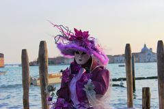 Venice Carnival Mask. Purple woman near the water stock photography